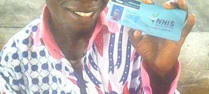 A smiling teacher holding up his goverment heath card