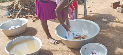 A young woman surrounded by basins of clothes and dirty water bends over a bowl of soapy clothes