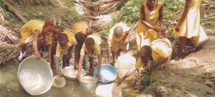Children at the stream fill buckets, basins and pitchers